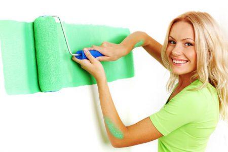 mujer pintando pared de color verde