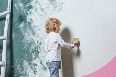 niño pintando pared de una habitación