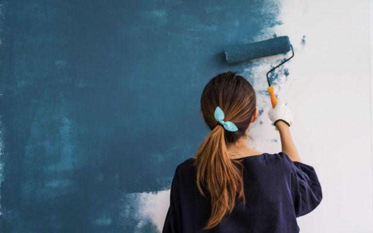 mujer pintando pared de color azul